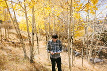a man standing alone in a fall forest reading a Bible