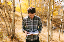 Man Outside Reading Bible During Fall