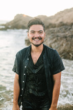 smiling man soaking wet standing on a shore