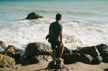 a man walking on a rocky shore