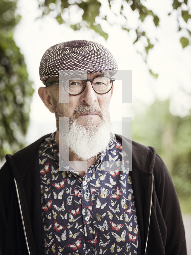 an elderly man with a beard wearing a hat and glasses