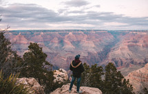 a man standing at the edge of a cliff taking in the view of canyons