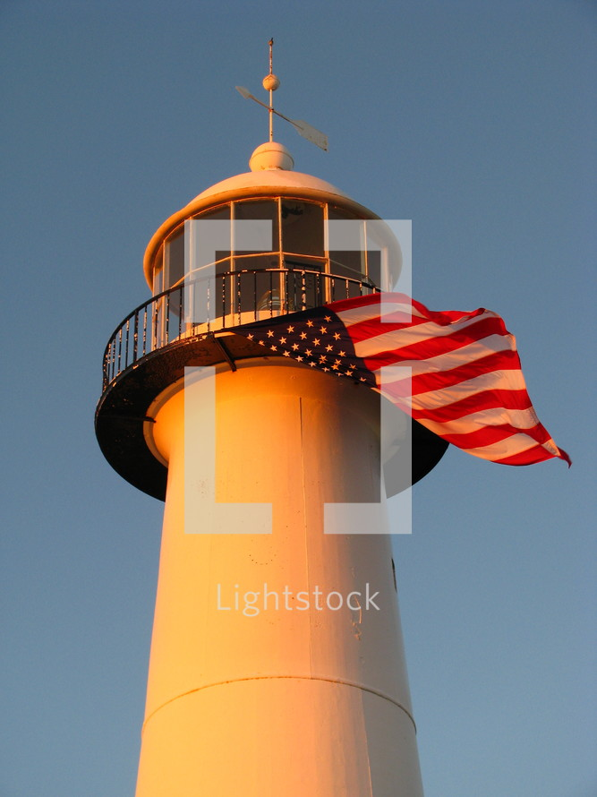 top of a lighthouse, with an American flag blowing in the wind