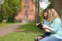Young women smiling while reading in the bible together outside on a sunny day with a cathedral in the background.