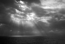 sunlight through the clouds shining onto the ocean