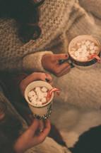 women holding mugs of hot cocoa
