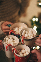 mugs of hot cocoa and candy canes