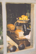 view into a kitchen through a window of lemons and bread