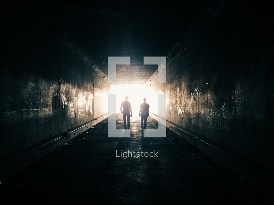 two men walking towards light at the end of a tunnel