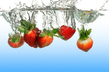 Strawberries submerged into water creating a splash.