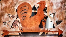 Rusted metal rooster sign.