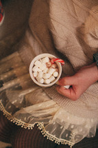 girl holding a mug of hot cocoa and marshmallows