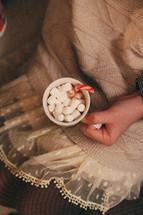girl holding a mug of hot cocoa and marshmallows
