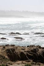 Ocean waves crashing onto rocks on a hazy day.