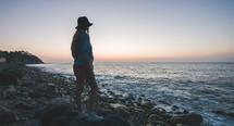 woman standing on a rocky beach