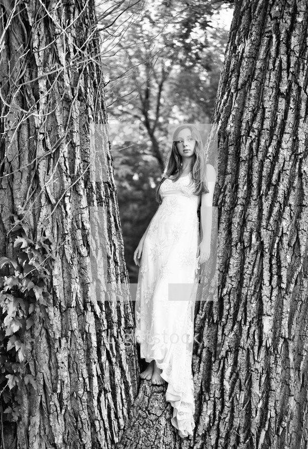 A woman in a white dress standing in a tree
