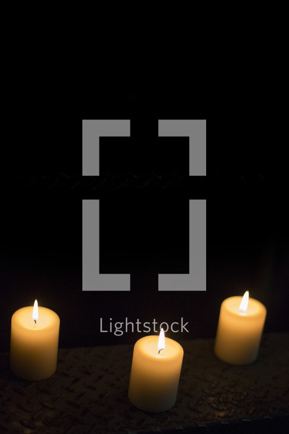 Three white votive candles with flame.