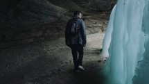 a man walking in a cave looking at a frozen waterfall