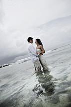 bride and groom standing in water