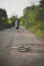Man walking away from crutches on dirt road.