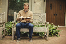 Man on bench reading Bible