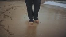 a man walking barefoot on a beach
