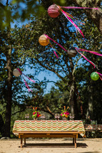 Outdoor table set with table linen wine glasses under oak trees with paper lanterns