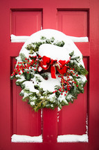 snow on a Christmas wreath on a red front door