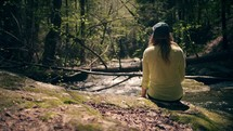 a woman sitting outdoors listening to water flow in a stream