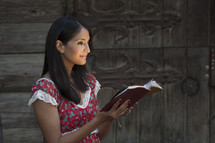 woman standing reading a Bible with her face glowing