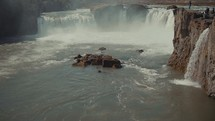 tourists watching a rushing waterfall