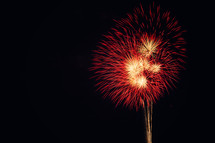 Red and gold fireworks exploding in the night sky.