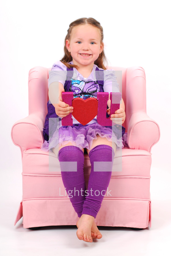 "Young girl sitting in pink chair holding ""I love you"" sign."