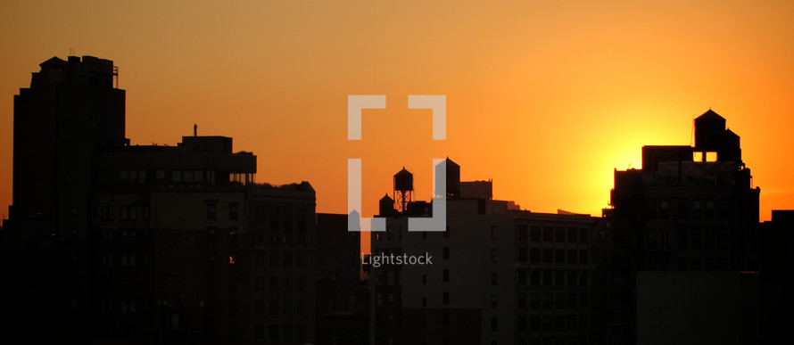 glow of the sun at sunset behind city buildings