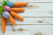 Easter eggs and carrots decorations on wood