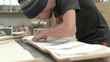 man designing a wooden skateboard
