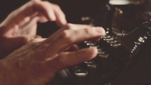Hands typing on a vintage typewriter.