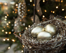 gold eggs in a bird's nest in a Christmas tree