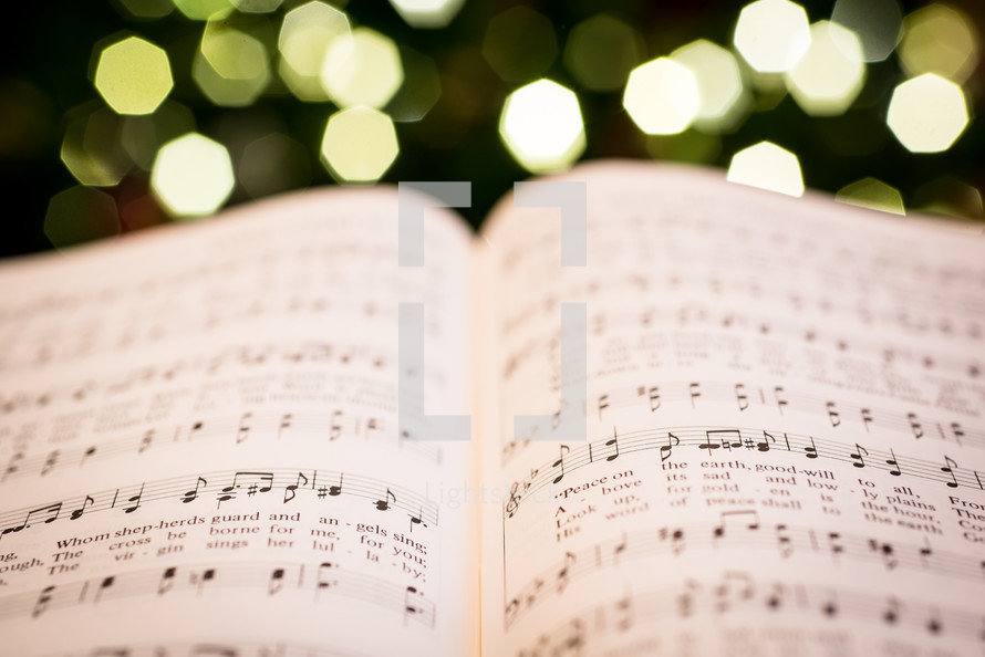 open pages of a hymnal and Christmas tree