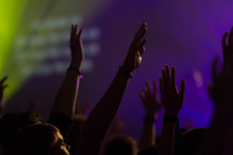 teens with raised hands at a worship service