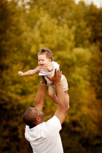 father hold his infant daughter in the air