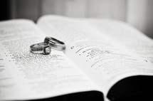 wedding rings on pages of a Bible