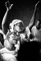 A woman with hands raised during corporate worship