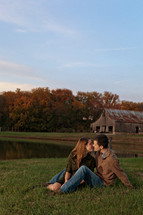 Man and woman kissing while sitting on grassy meadow by pond with barn in the background.