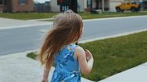 child walking on a sidewalk