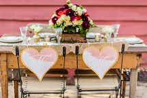 A rustic  table setting for a bride and groom wedding decor table setting hearts