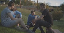 young men sitting outdoors talking