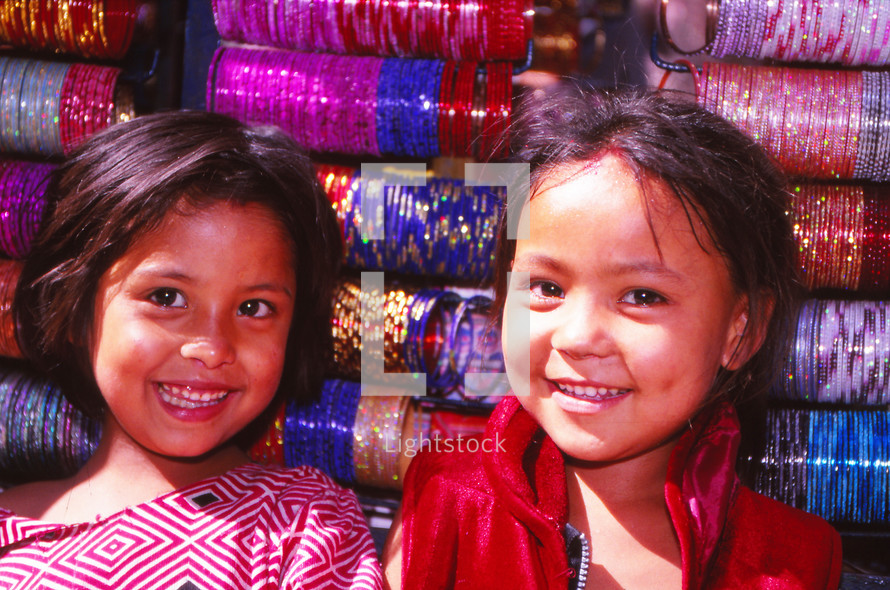 smiling young girls in front of spools of yarn