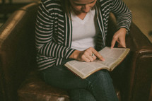 Woman sitting in chair with legs crossed studying the Bible.