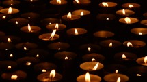 votive prayer candles in the darkness of a church